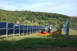 das Photo zeigt einen Traktor, der zwischen zwei Reihen von Photovoltaikmodulen eine Wiese mäht.